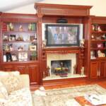 This Cherry wood wall unit features intricately carved moldings and corbels, an elaborate fireplace mantle and granite surrounding the fireplace.