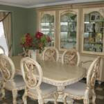 This old world styled dining room set is antiqued sprayed an off-white lacquer and hand brushed in our antique umber glaze.  The dining room table is hand carved and features seating for 10 with a removable leaf.  The breakfront features hand carved raised panel doors, glass doors, glass shelves...